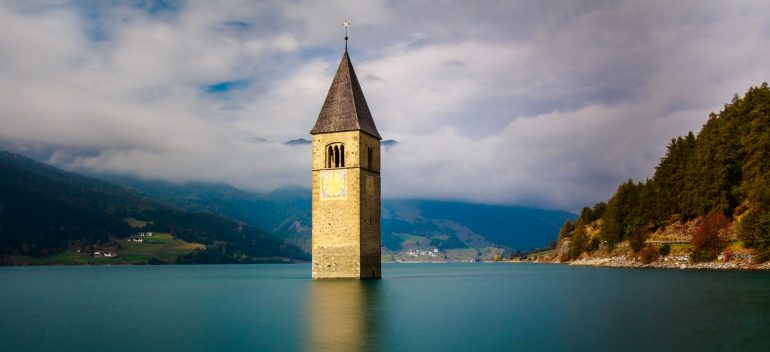 A bell tower underwater rising out of a lake.