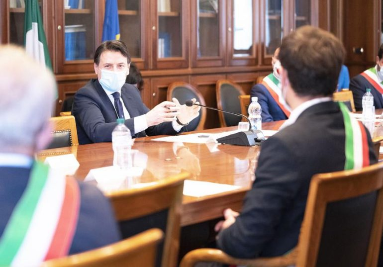 Prime Minister Conte at a table with other politicians during the pandemic..